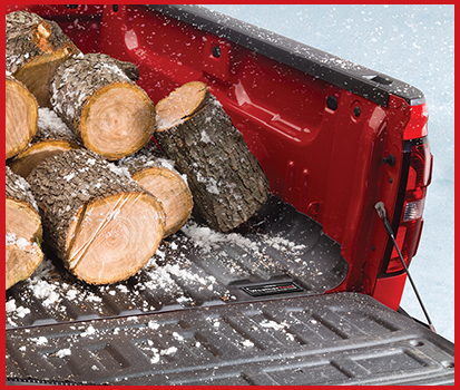 Image shown of a truck outside in the snow with fire wood in the bed of the truck resting on top of a TechLiner.