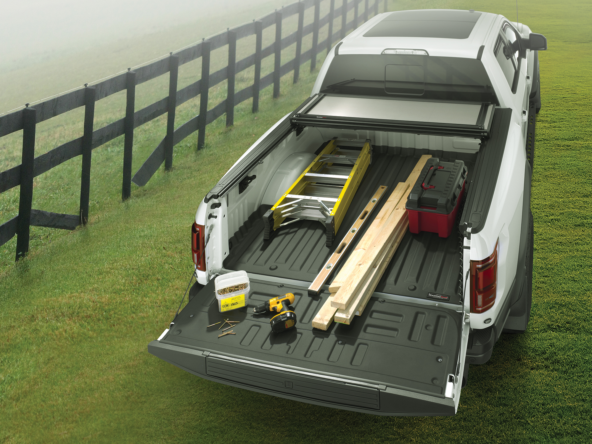 Pick Up truck on a ranch with a drill, plywood, toolbox, and ladder on top of the WeatherTech TechLiner