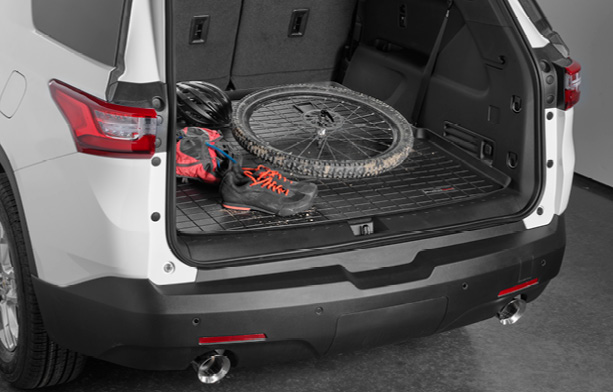 Black WeatherTech Cargo/Trunk Liner with a dirty bicycle wheel, helmet, shoes and other biking gear on top.