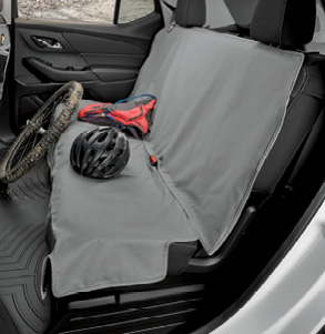 Dirty bike wheel, bike helmet and other biking gear on top of a dirty grey WeatherTech Seat Protector.