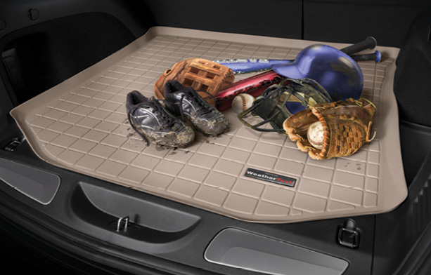 Tan WeatherTech CargoLiner with dirty cleats and a variety of other sports equipment on top.