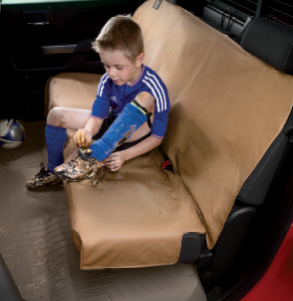 Child untying their dirty soccer cleats while in back seat of a vehicle sitting on a tan WeatherTech Seat Protector.