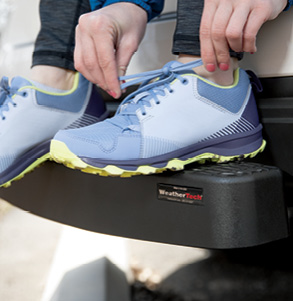 Person tying their shoes while resting their feet on Bumpstep XL.