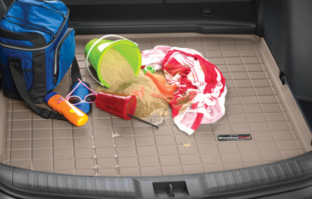 Tan WeatherTech CargoLiner with a towel, spilled water, spilled sand bucket, cooler and sun screen.
