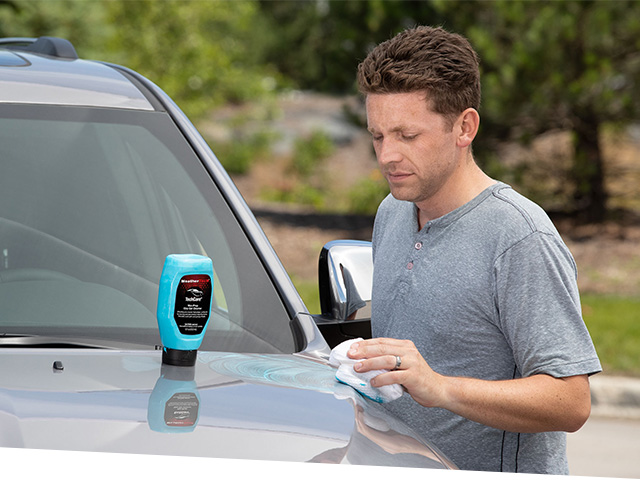Man waxing silver car with Wax-Prep Clay Gel Cleaner bottle sitting on hood of car.