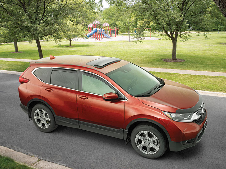 WeatherTech Side Window Deflectors and Sunroof Deflectors installed on a Red Honda CRV parked across the street from a playground.