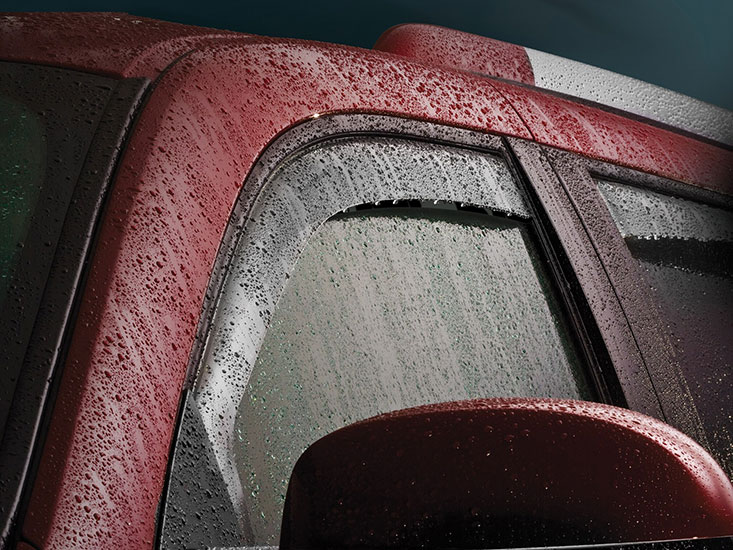WeatherTedh Side Window Deflectors installed on a red SUV, covered in rain water.