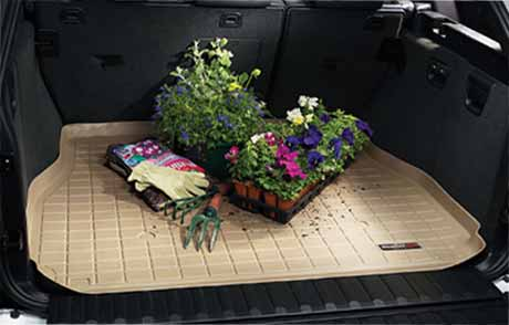 Tan WeatherTech CargoLiner with flowers, potting soil, spilled dirt and gardening tools placed on top.