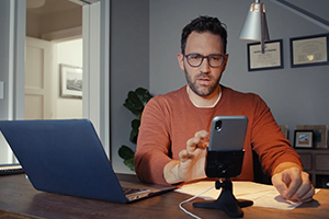 A man sitting in home office while looking at DeskFone