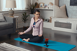 A women doing yoga while looking at DeskFone