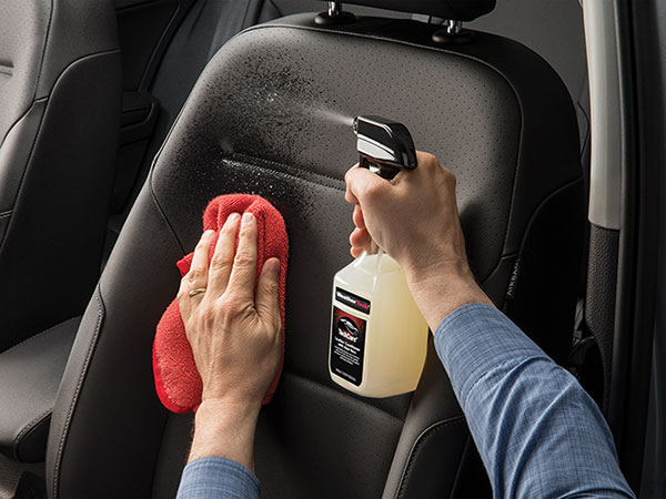 Person cleaning interior of a car