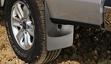 Mudflap installed on vehicle with muddy tire.