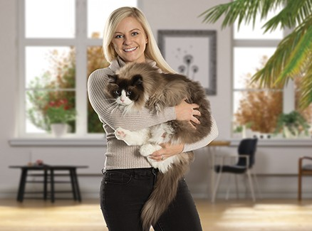 A young woman holding a fluffy cat.