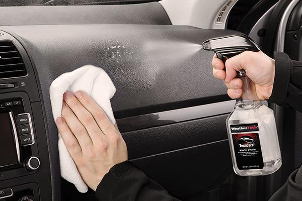 Spraying Interior Detailer on the car's dashboard
