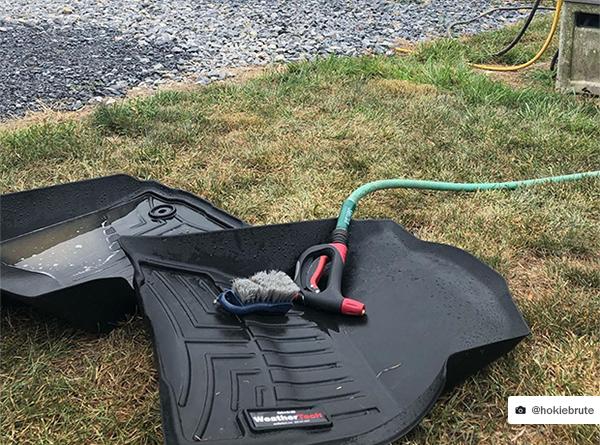 A wet weathertech floorliner on grass with garden hose
