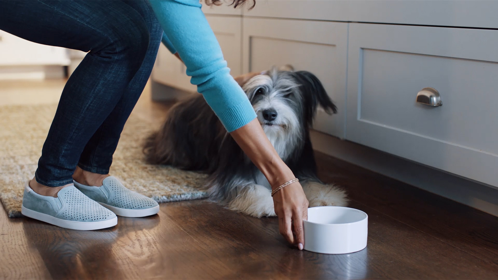 Woman picking up ceramic pet food bowl.