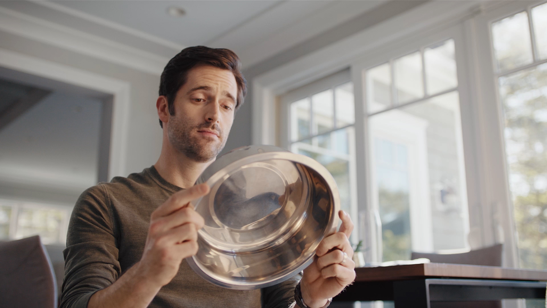 Man checking the underside of his pet's food bowl to see if it is safe.